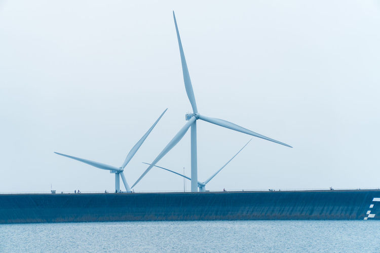 Wind turbines by sea against clear sky