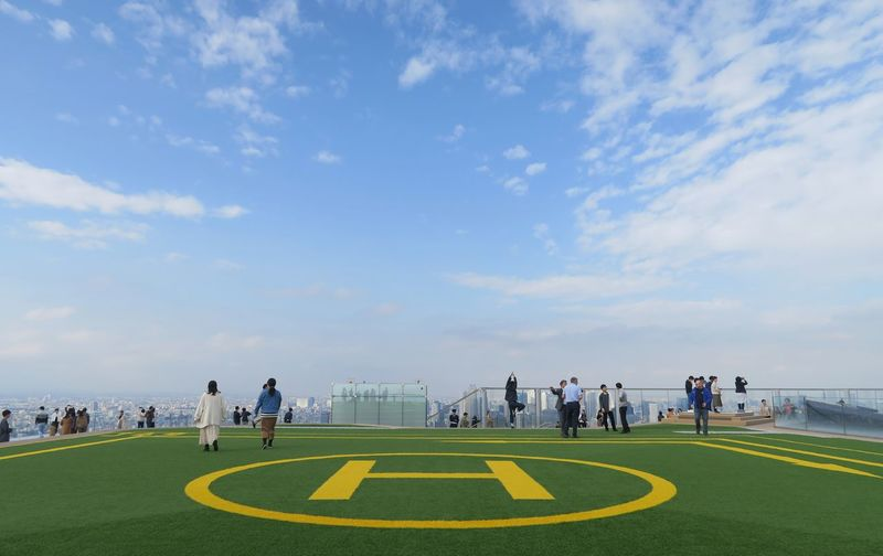 People playing soccer field against sky