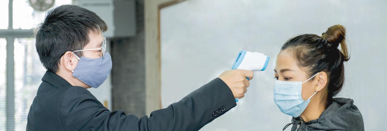 Man wearing flu mask checking temperature of woman