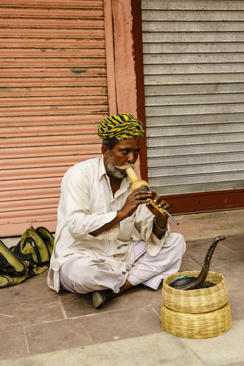 Life and city scenes in Jaipur, India India Indian Culture  Jaipur Jaipur Rajasthan Snake Charmer Travel Photography Adult Basket Building Exterior cityscapes Day Front View Indiapictures Men One Man Only One Person Outdoors People Real People Sitting Street Photography Tourism Destination Turban Young Adult