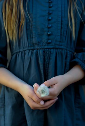 Midsection of girl holding dandelion