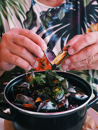 Midsection Of Person Eating Mussel