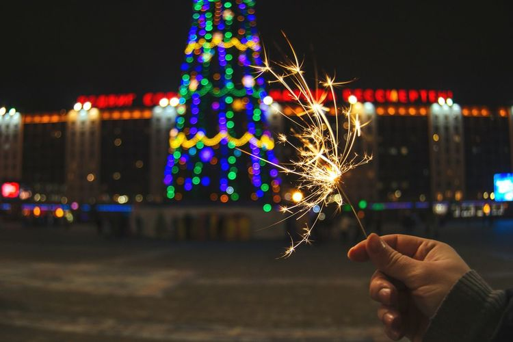 From My Point Of View By Ivan Maximov Eyeem Photo The Week On EyeEm New Year Around The World New Year Crismas Tree Night Lights Christmas Lights Belarus City Vitebsk,Belarus Great Outdoors Composition Focus On Foreground In Hand Multicolored Background Perspective Night Celebration Human Hand Human Body Part Illuminated Arts Culture And Entertainment Holiday - Event Firework - Man Made Object Outdoors One Person Multi Colored Cityscape City