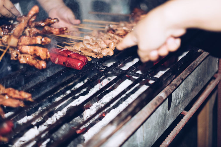 Cropped hands preparing food on barbecue grill
