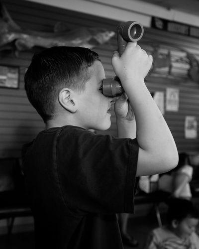 Boy looking through periscope in classroom