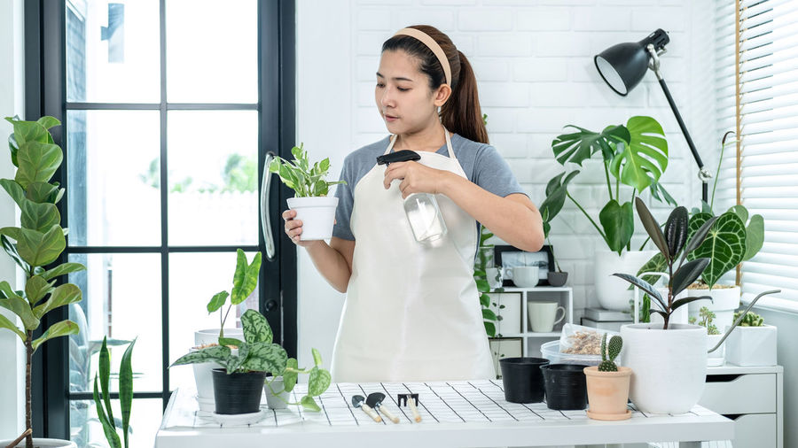 Young woman standing by potted plants
