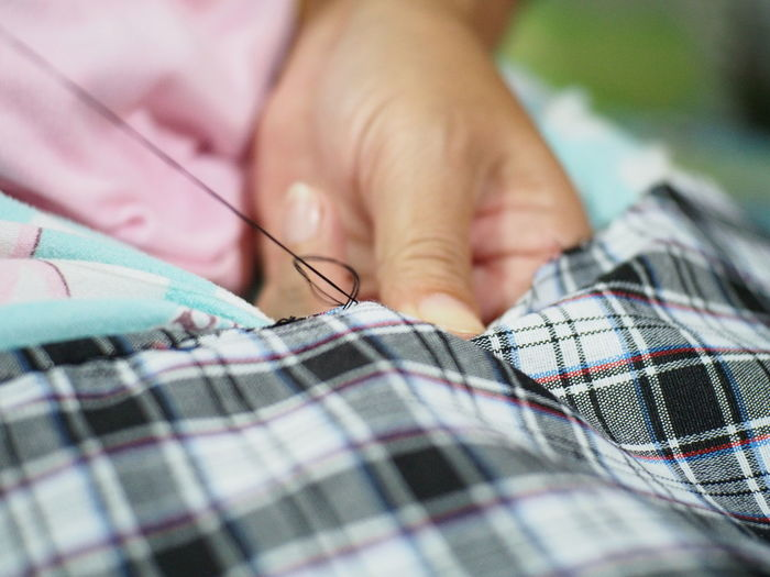 Cropped Hands Of Woman Stitching Fabric