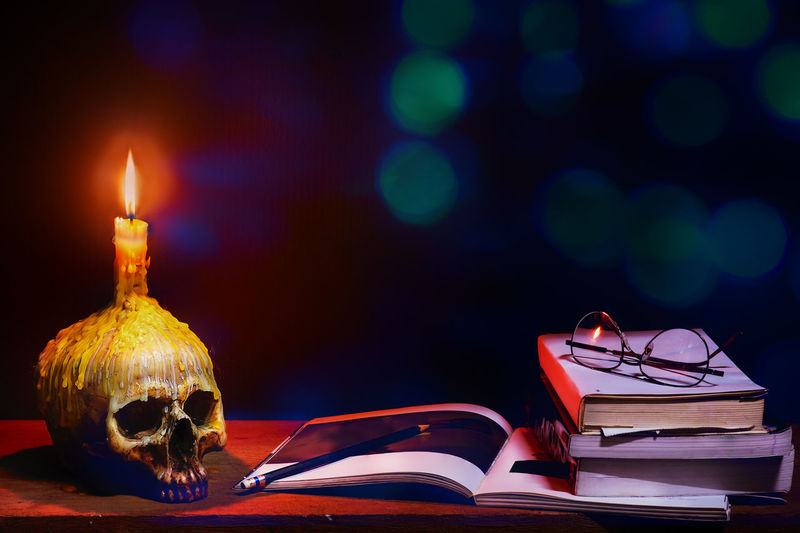 Close-up of illuminated candle and books on table