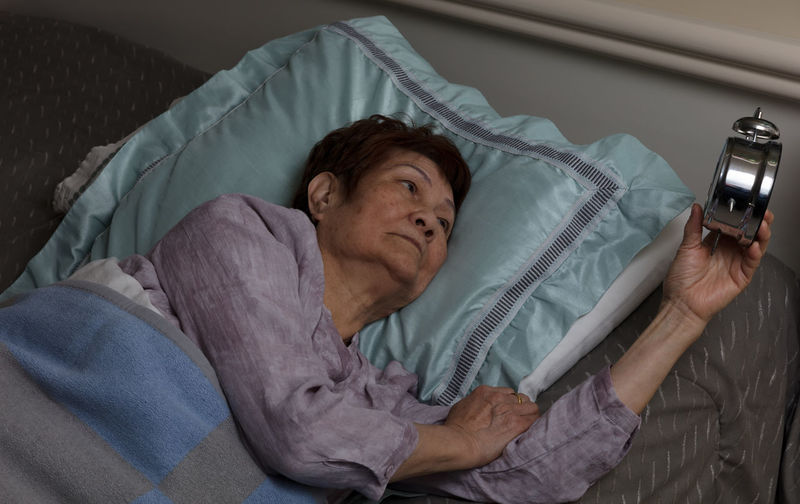 High angle view of senior woman holding alarm clock while lying on bed at home
