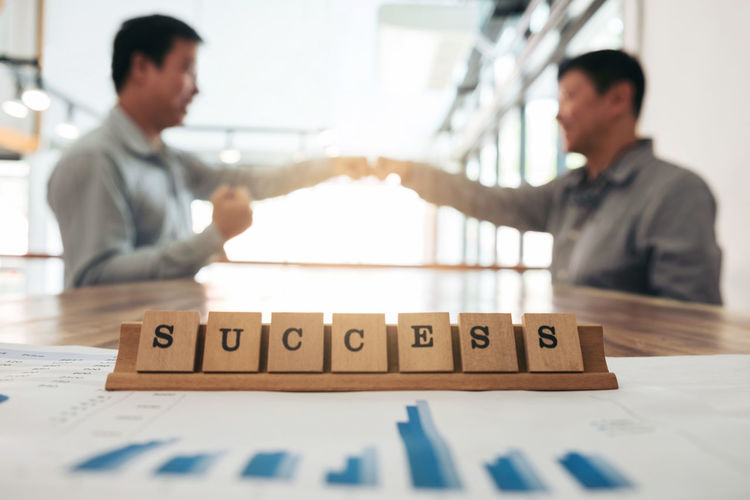 Close-up of success text against businessmen fist pumping at desk