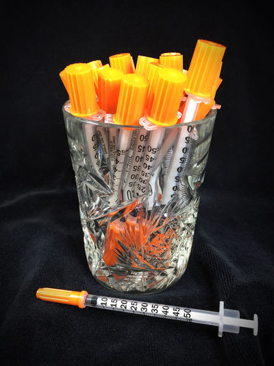 Close-Up Of Insulin Syringes In Crystal Glass On Fabric