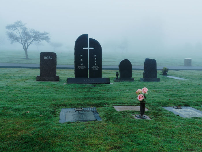 Tombstones and flowers in cemetery during foggy weather