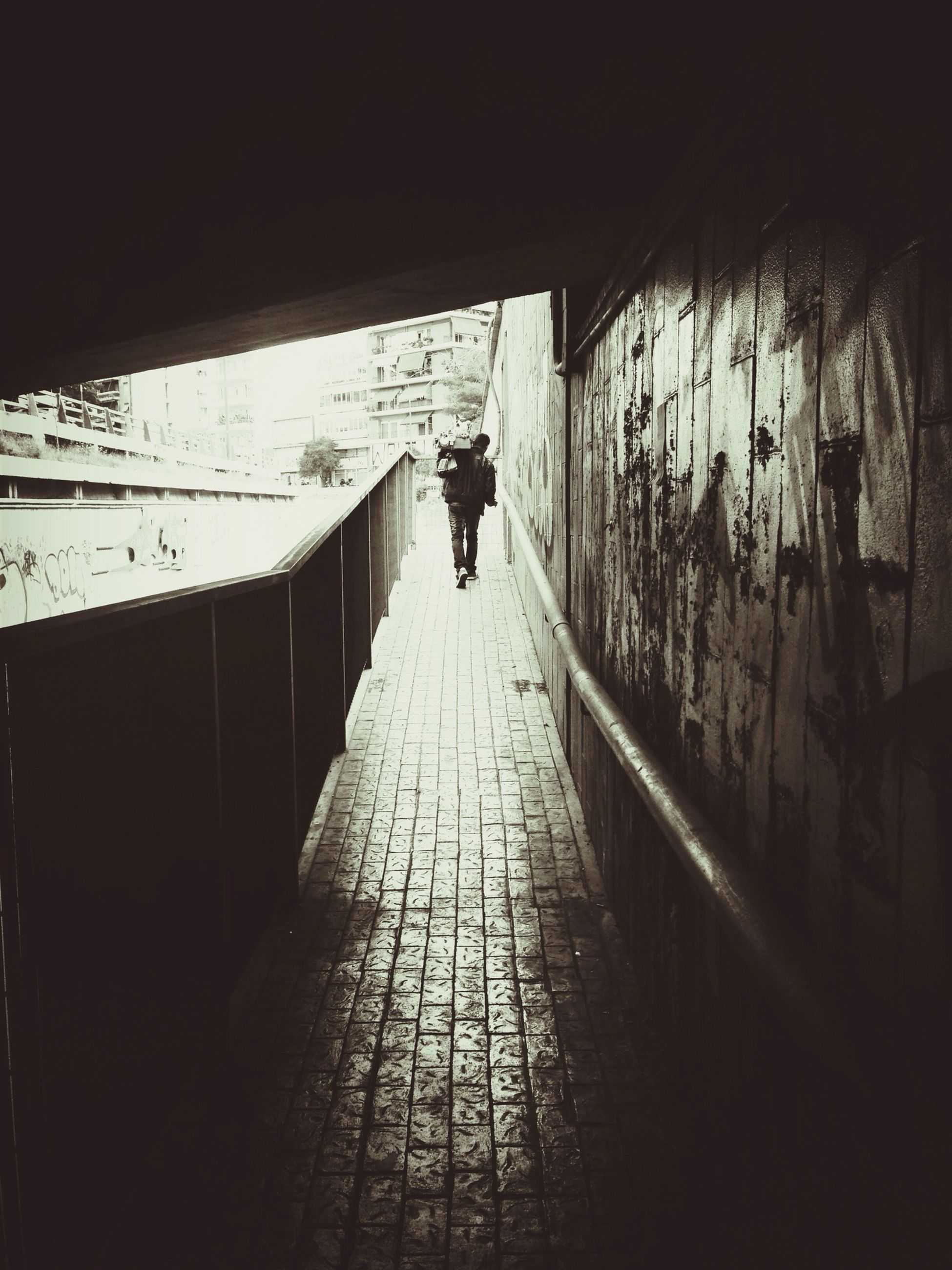 full length, walking, the way forward, rear view, indoors, lifestyles, men, silhouette, architecture, built structure, diminishing perspective, tunnel, leisure activity, corridor, person, narrow, wall - building feature