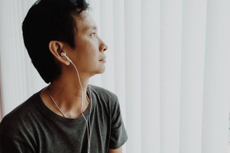 Close-up of man listening to music against white blinds