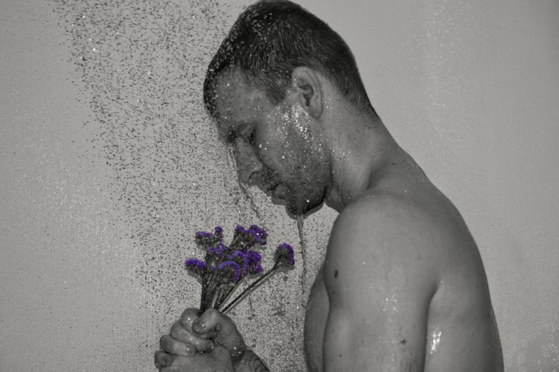 Side view of man bathing with flowers