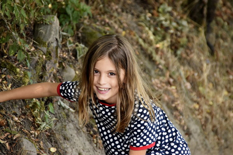 High angle portrait of cute cheerful girl in forest