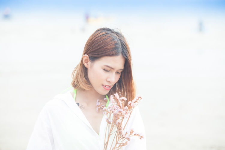 Adult Adults Only Beautiful People Beautiful Woman Beauty Brown Hair Close-up Day Dry Flowers Eyes Closed  Focus On Foreground Holiday Looking Down Nature One Person One Woman Only One Young Woman Only Outdoors People Sea And Sky Sea Fashion Standing Women Young Adult