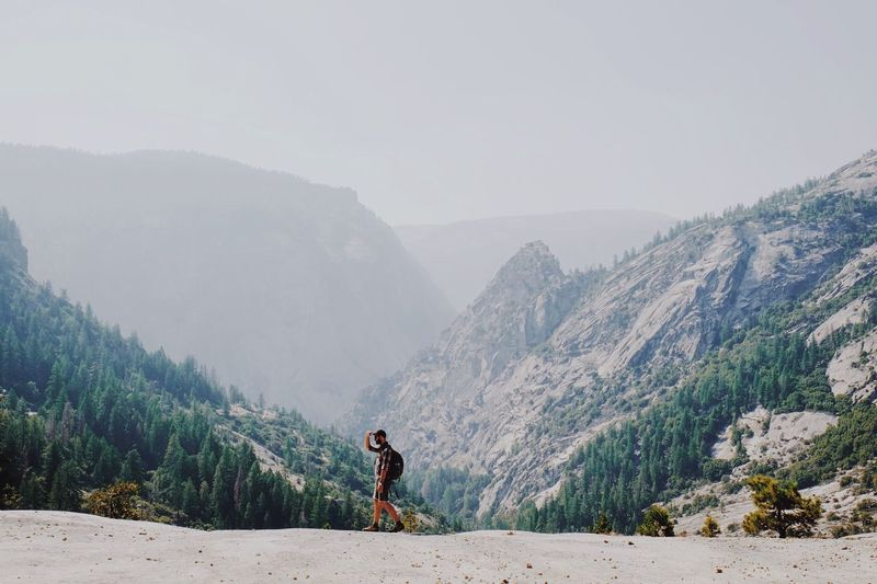Man standing on field against mountains in foggy weather