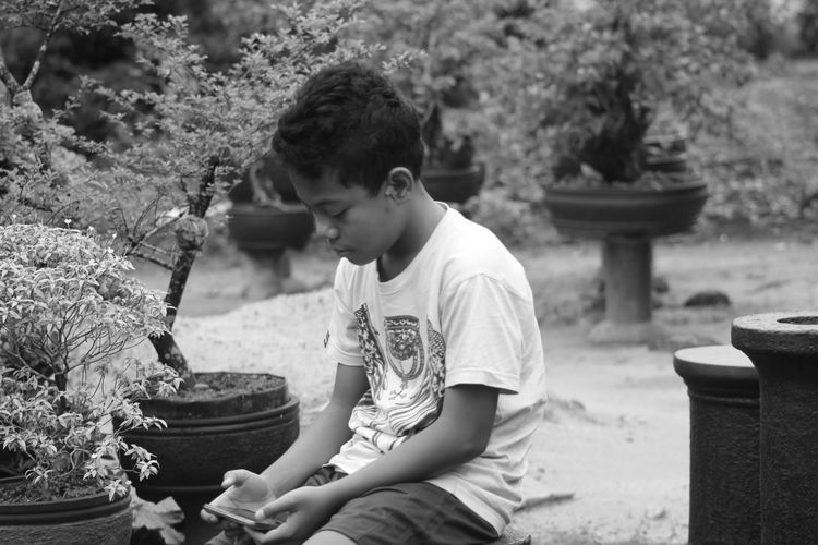 Boy using smart phone while sitting outdoors