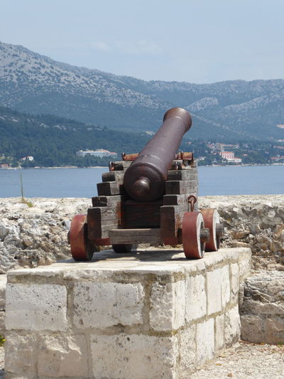 Cannon by sea against sky