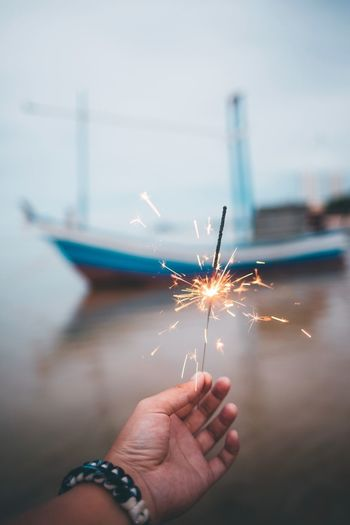 Cropped image of hand holding sparkler at night