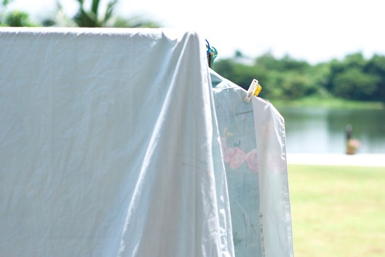 Clothes and flat sheet hanging on the clothesline with clothespin for drying from the heat of sun