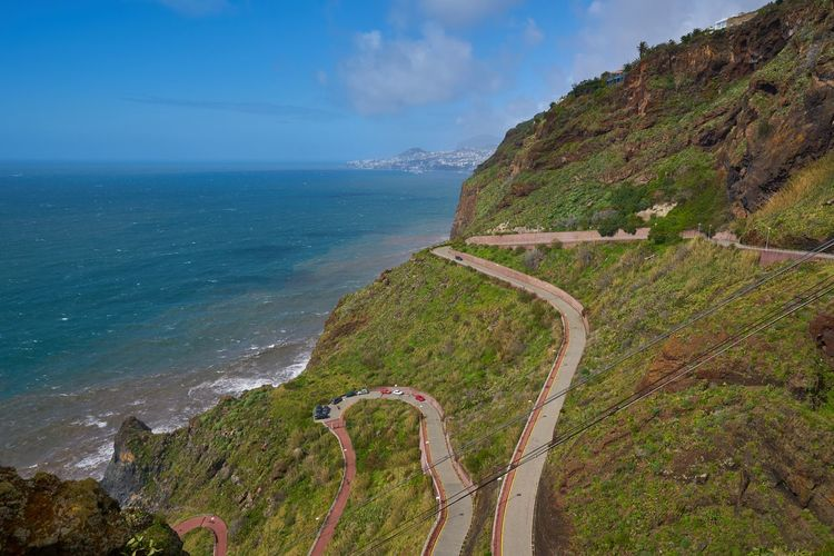 Aerial view of a road with many curves in Caniço, Madeira on the coastline Madeira Travel Island Portugal Portuguese Europe Landscape Nature Outdoors Aerial View Aerial Panorama Panoramic Rock Red Seascape Sea Ocean Atlantic Scenics Horizon Mountain Cost Coastline Shore