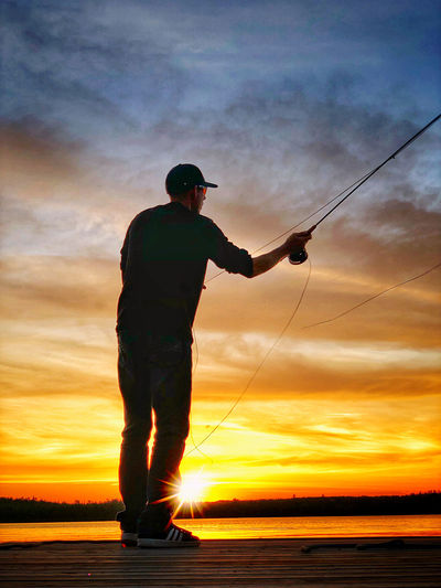 Silhouette man fishing against sky during sunset