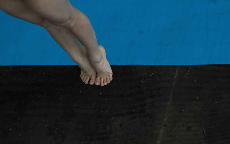 Low section of woman tiptoeing on poolside