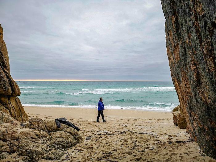 casually walking by Frame It! Winter Stroll Woman Walking Along The Beach Water Wave Sea Full Length Beach Sand Sky Horizon Over Water Cloud - Sky Low Tide Seascape Shore Coastline Rocky Coastline Sandy Beach
