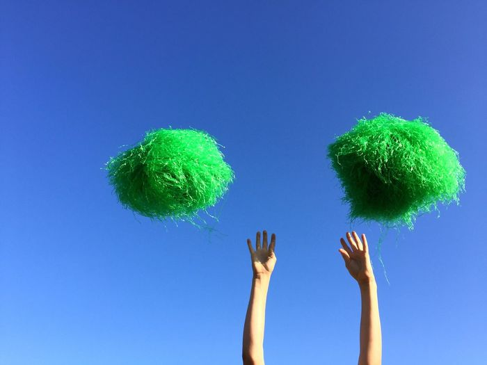 The Color Of Sport Green Pompoms Blue Sky Copy Space Hands In The Air Minimalism Cheerleading Vibrant Color Outdoors Simplicity Day One Person Low Angle View TakeoverContrast