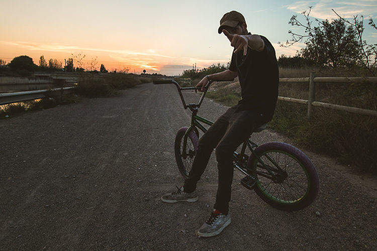 Man gesturing shaka sign while sitting on bicycle against sky during sunset