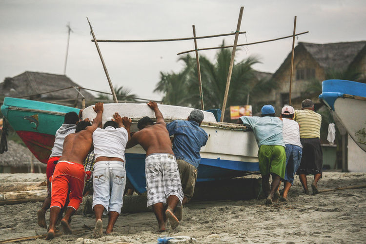 Rear view of people pushing boat at sandy beach