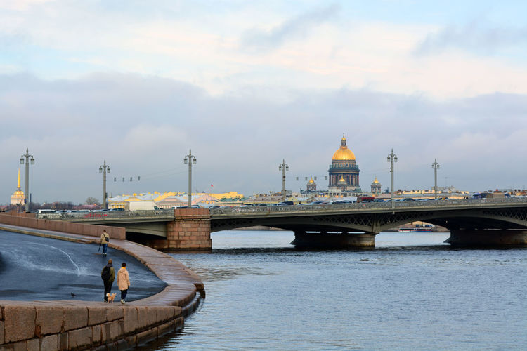 Blagoveshchensky bridge over neva river with saint isaac cathedral against cloudy sky