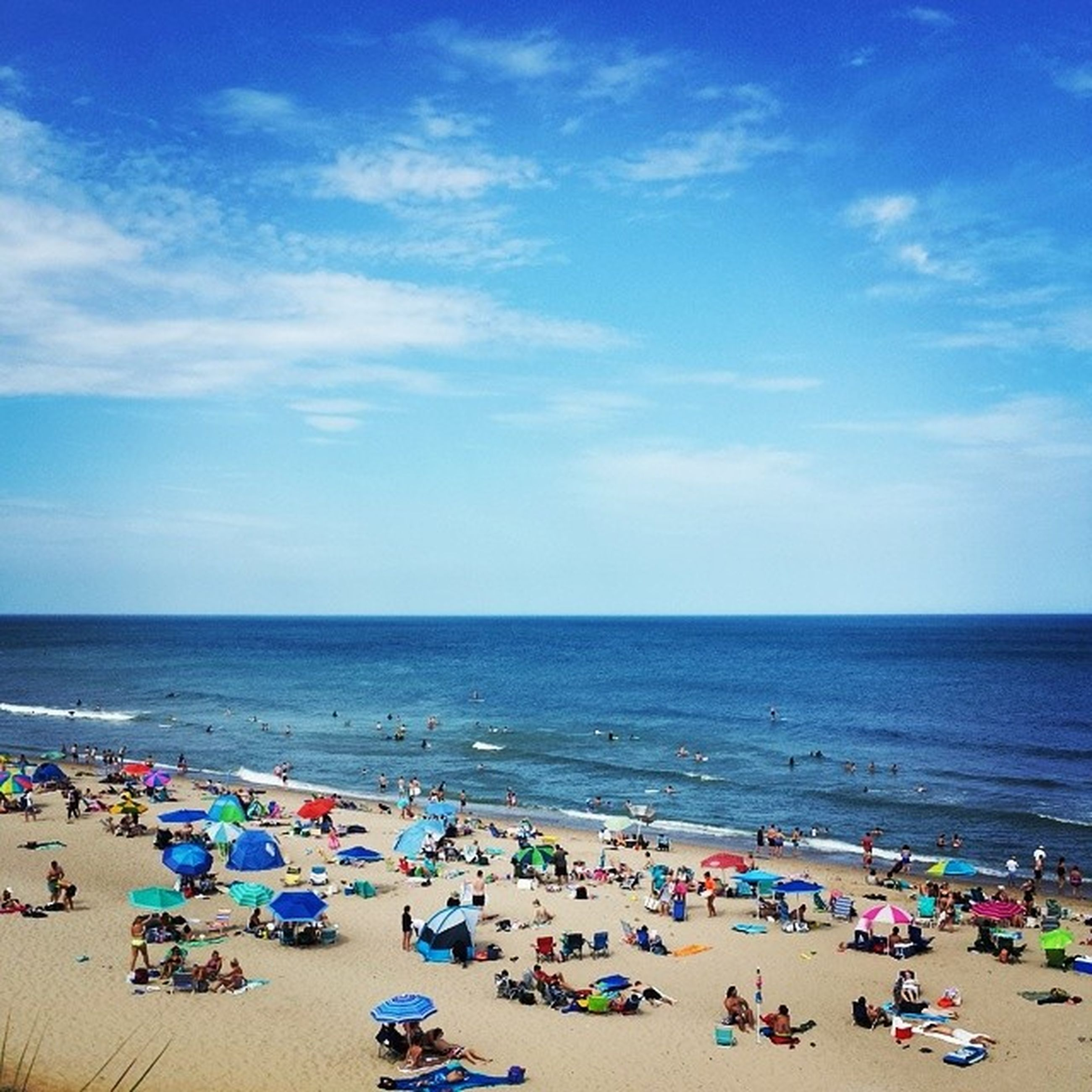 sea, beach, horizon over water, large group of people, water, shore, sand, vacations, sky, relaxation, leisure activity, mixed age range, summer, person, lifestyles, enjoyment, blue, beach umbrella, scenics