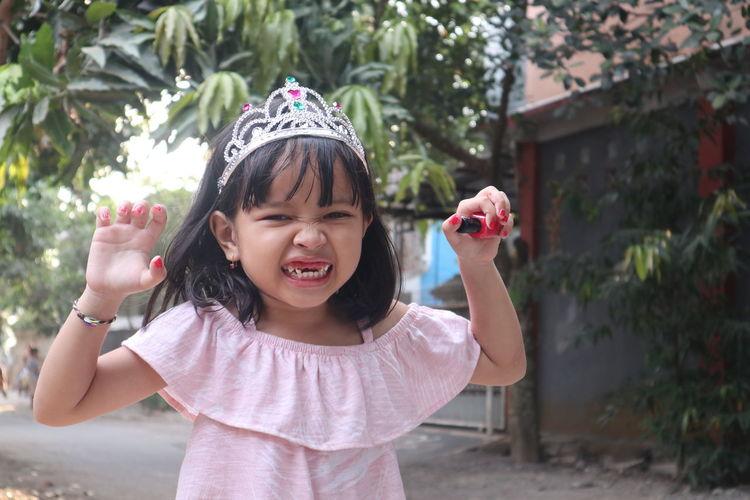 Portrait of girl clenching teeth while holding nail polish at yard