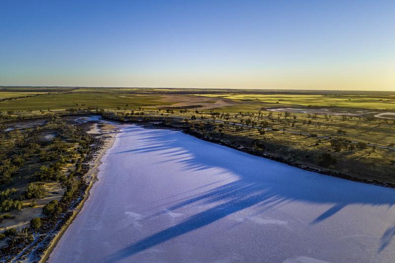 Sunset casting long tree shadows on salt lake hardy. murray-sunset national park,  australia