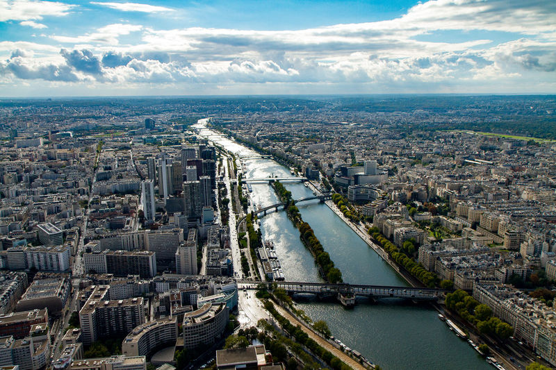 Aerial view of seine river amidst cityscape against sky