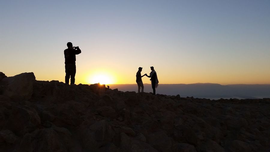 Man Taking Picture Of Couple Against Clear Sky And Mountain