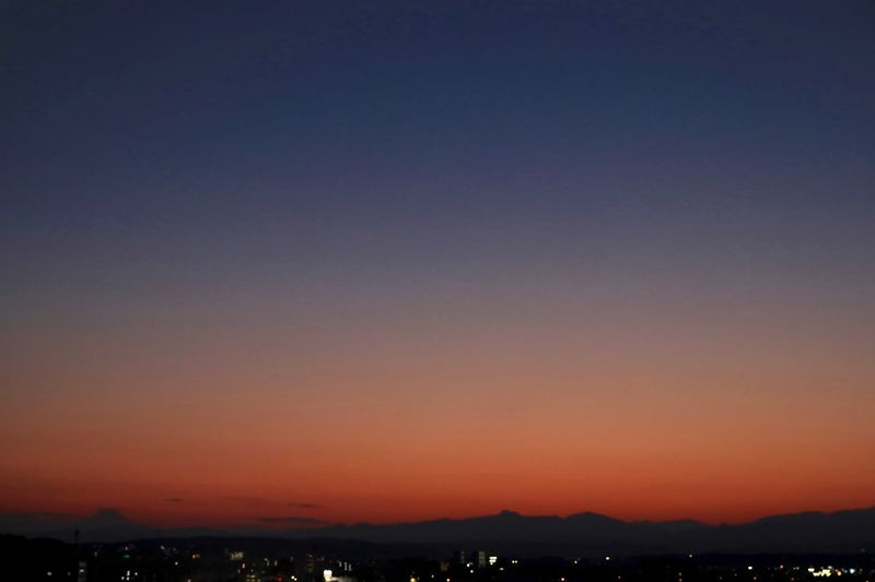 Scenic view of silhouette city against clear sky at sunset
