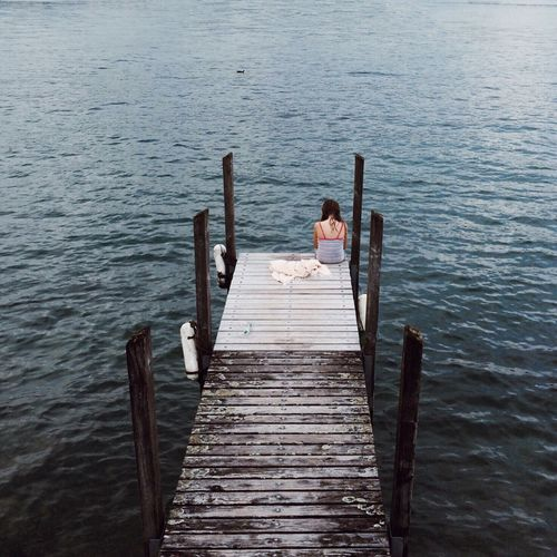 High angle view of woman sitting on pier over calm lake
