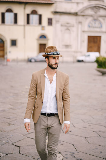 Young man wearing hat looking away on street
