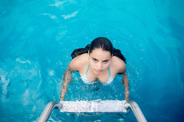 Portrait Of Young Woman Holding Railing In Swimming Pool