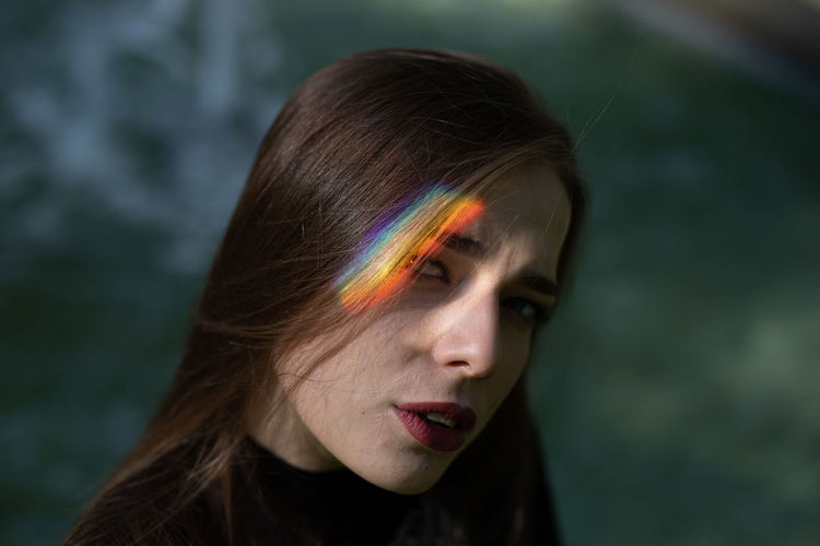 Close-up portrait of young woman with spectrum