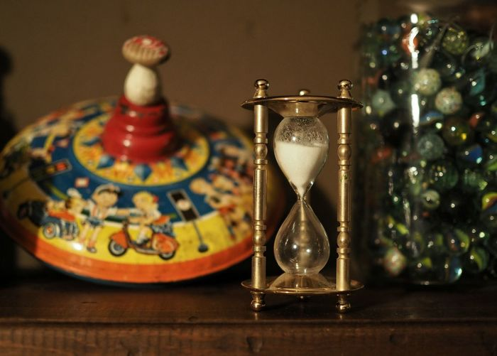 Hourglass With Toy And Marbles In Jar On Table At Home