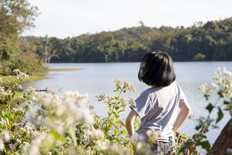 Rear view of woman standing by plants while looking at lake