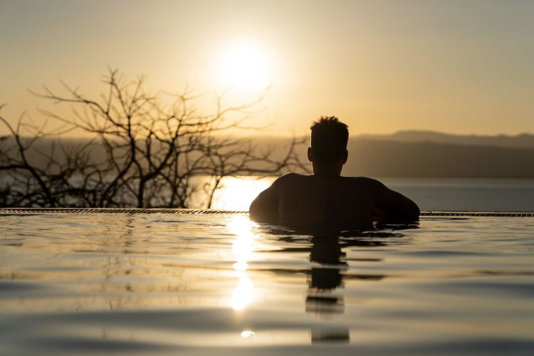 Silhouette man in infinity pool against sky during sunset