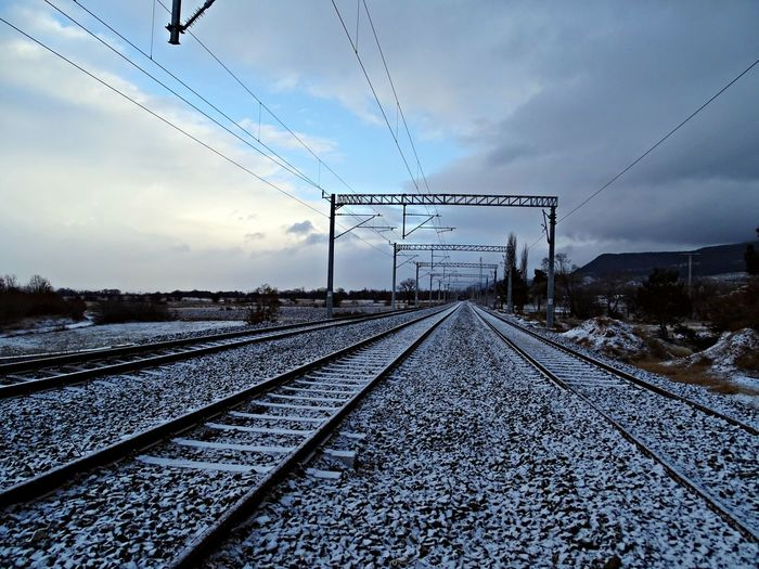 Railroad tracks against cloudy sky during winter