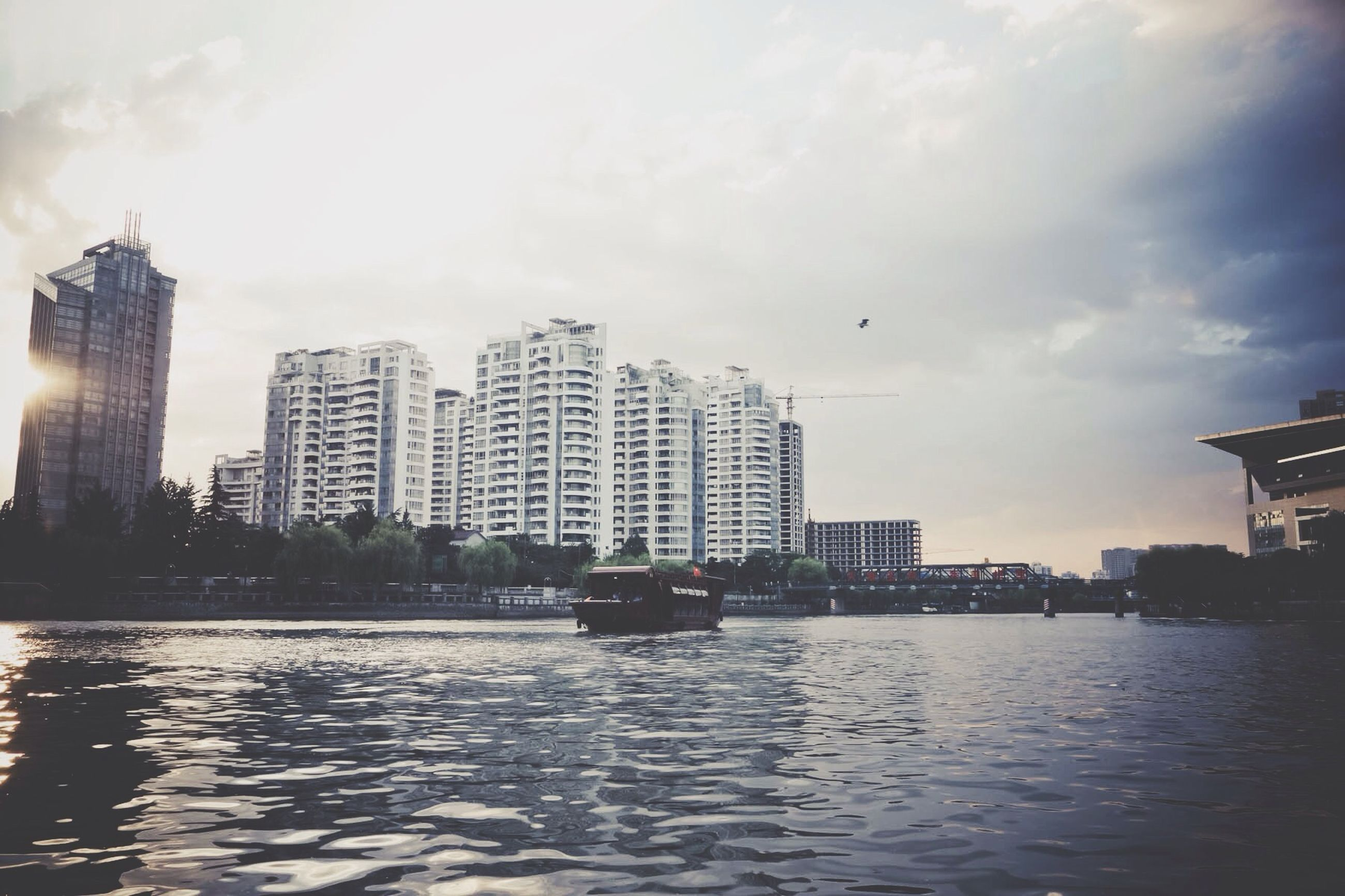 building exterior, architecture, built structure, water, waterfront, sky, city, cloud - sky, river, reflection, skyscraper, building, rippled, cloud, cityscape, cloudy, urban skyline, outdoors, no people, residential building