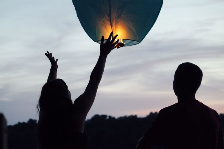 Woman flying lit paper lantern during sunset